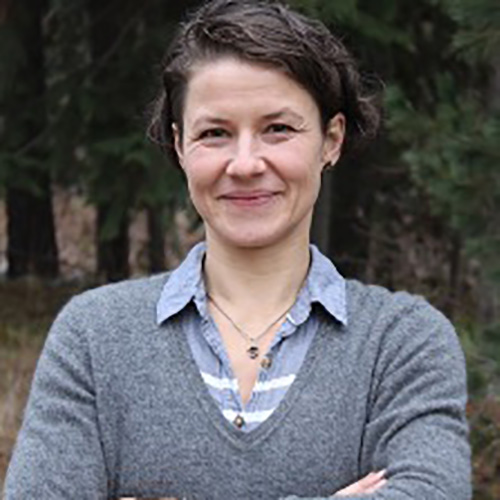 A photo of Sonja Thoma standing with her arms crossed, wearing a grey sweater