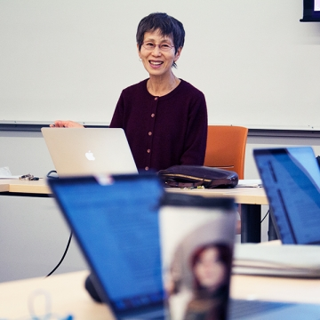 A picture of Professor Ryuko Kubota in class, laughing, sitting in front of a laptop computer