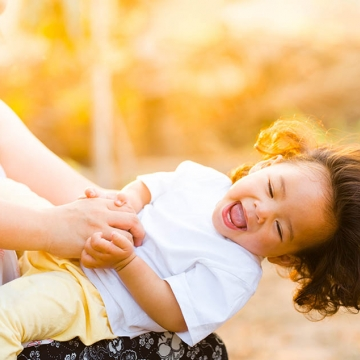 An image of a parent holding a laughing child, who is leaning almost horizontal, with sunlight in the background