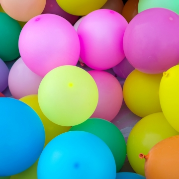 A picture of many different coloured balloons grouped together, including pink, blue, orange, green and yellow balloons.