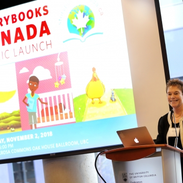 An image of Bonny Norton standing at a podium in front of a projector screen, at the launch of Storybooks Canada,
