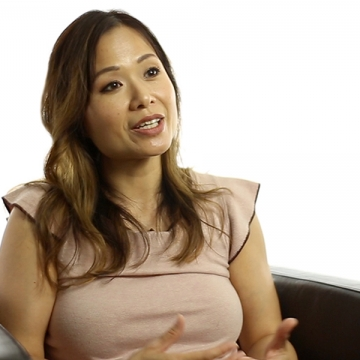 An image of Dr. Brenda Poon speaking, sitting on a sofa, in front of a white screen