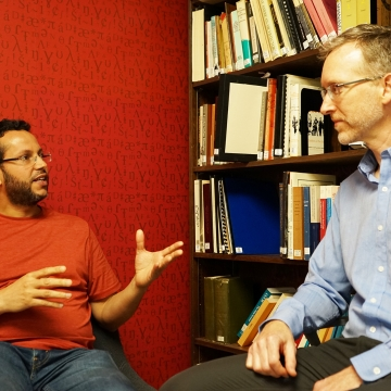 A picture of assistant professor Muhammad Abdul-Mageed speaking and Professor Bryan Gick listening against a red wall, with a bookcase in the background