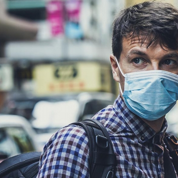 An image of a man wearing a surgical mask in a busy street