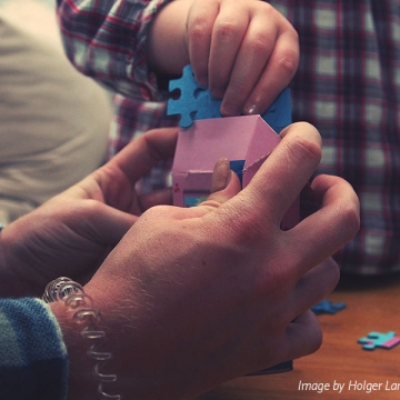 A close up on an adult's hands holding a pink box, with a child's hand placing a blue puzzle piece in the box