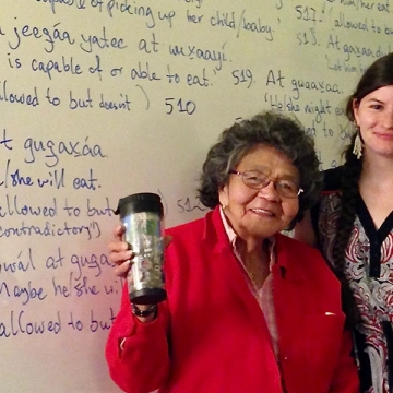 A picture of Elder Keiyishí Bessie Cooley, wearing a red jumper and raising a coffee travel mug, and Heather Burge wearing a dress with her arm around Elder Cooley. Both are standing in front of a whiteboard with Lingít and English on it