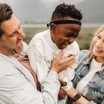 A picture of a mother and father lifting their child up in front of mountains. Everyone is laughing.