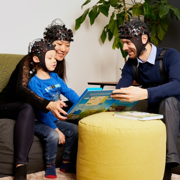 An image of parents reading a book to a child. Everyone is wearing EEG caps.