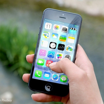 An image of a hand holding an iPhone above the ground, with apps showing on the screen