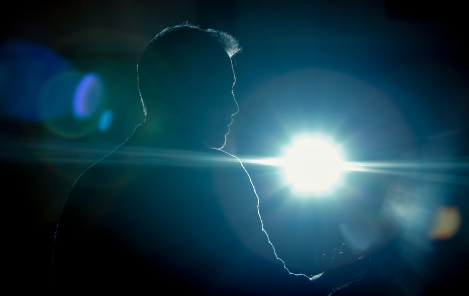 A photo of a mans silhouette, holding a phone, lit up by a spotlight