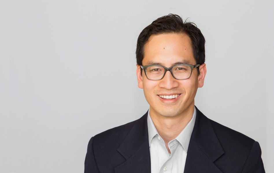 A headshot of Professor Edward Chang, smiling, wearing glasses, and standing against a grey background.