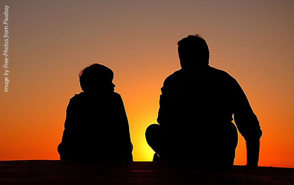 Silhouettes of an older man and child against the setting sun