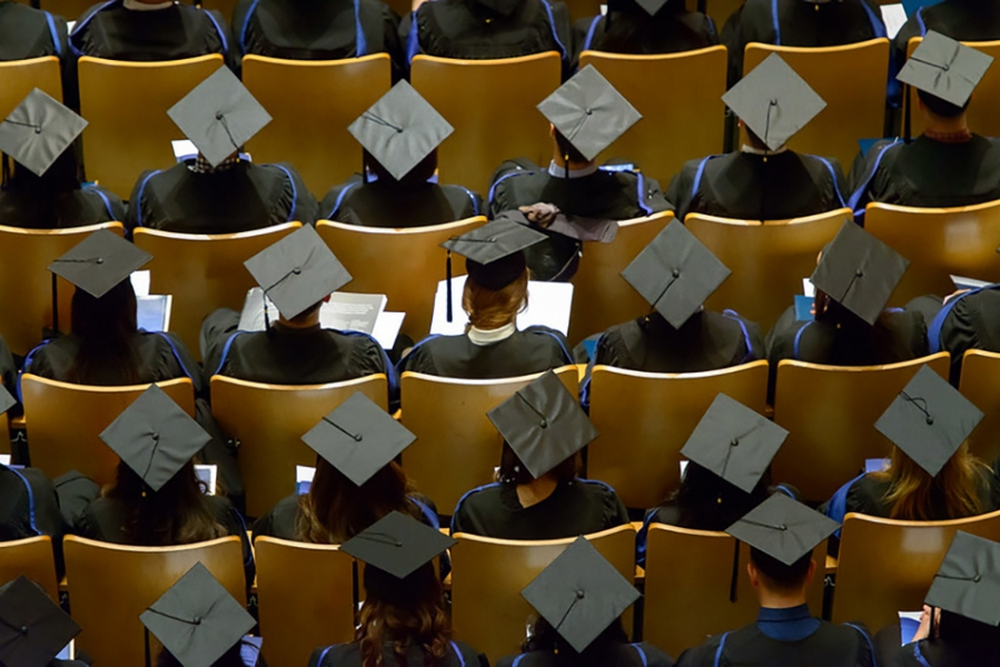 An eagle eye picture of UBC graduates sitting in rows facing forwards and wearing their graduation caps.