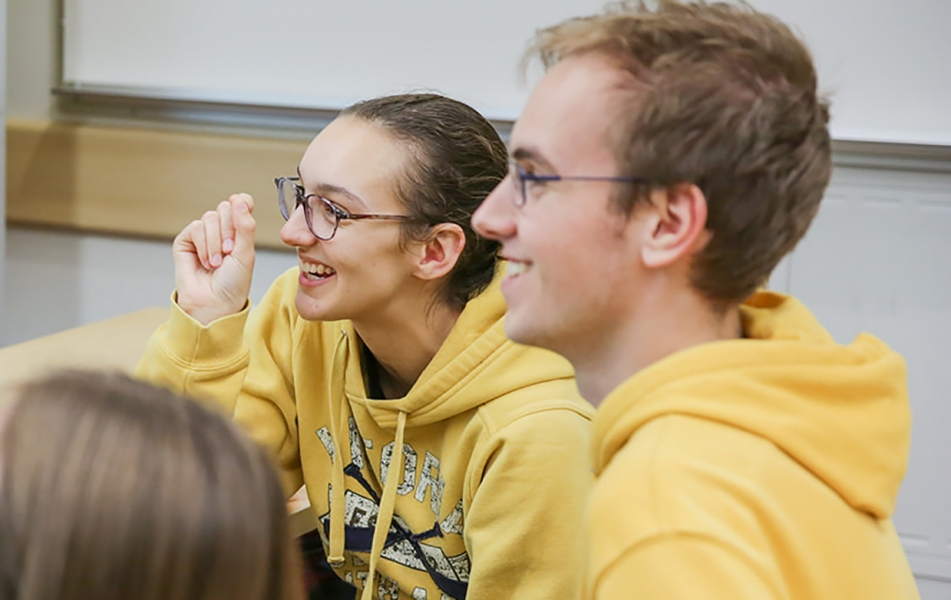 An image of Paris and Kelton, both wearing yellow jumpers, laughing in class