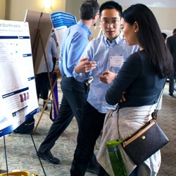 An image of Yadong explaining his poster to Rachel, with Bryan Gick in the background