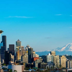 A photo of the Seattle skyline with blue sky and a mountain in the background