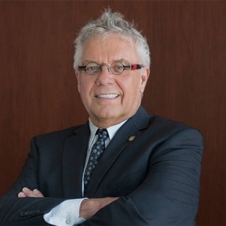 An image of Dean Blye Frank smiling, standing with arms crossed against a wooden panel wearing a suit and glasses