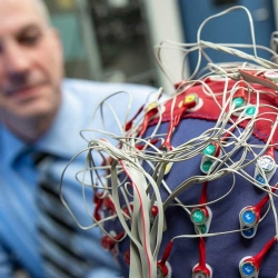 An image of Tony Herdman looking at a person wearing an EEG cap
