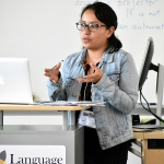 A picture of Ana Laura Arrieta Zamudio standing at a podium, gesturing with her hands. She is standing in front of a white board and laptop is on the podium. She is wearing a denim jacket and glasses.