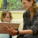 An image of Susan Birch holding an iPad in front of a child