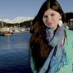 An image of Heather Burge standing in front of a harbour, wearing a green jumper and multicoloured scarf