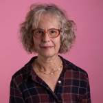 A headshot of Jan Edwards wearing glasses and standing against a pink background