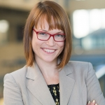 A headshot of Kiley Hamlin standing with arms crossed inside the UBC Psychology building