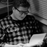 A black and white photo of Dr. Dallas Hunt reading a book in a plaid shirt