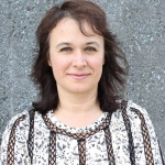A headshot of Stefka H. Marinova-Todd standing in front of a wall.