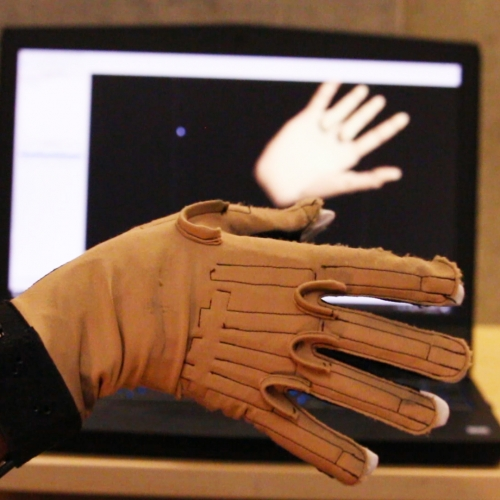 An image of the Cyberglove used to generate sound from movements, placed in front of a computer showing a 3D graphic of a hand