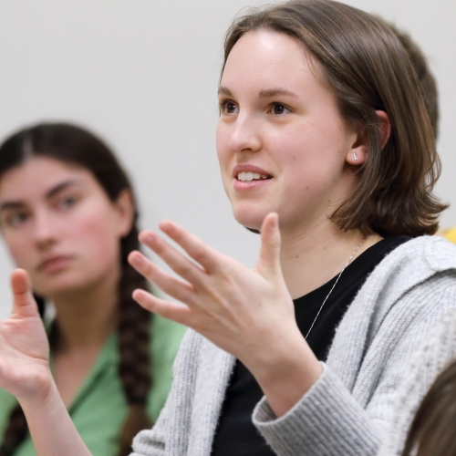 An image of Lauren speaking, gesturing with her hands, while classmates listen to her