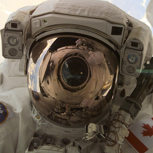 A through-the-window view of astronaut Chris A. Hadfield, STS-100 mission specialist representing the Canadian Space Agency, taken during the first extravehicular activity of the STS-100 mission.