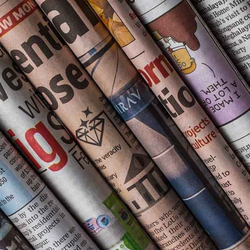 A photo of multiple newspaper spines piled on top of one another