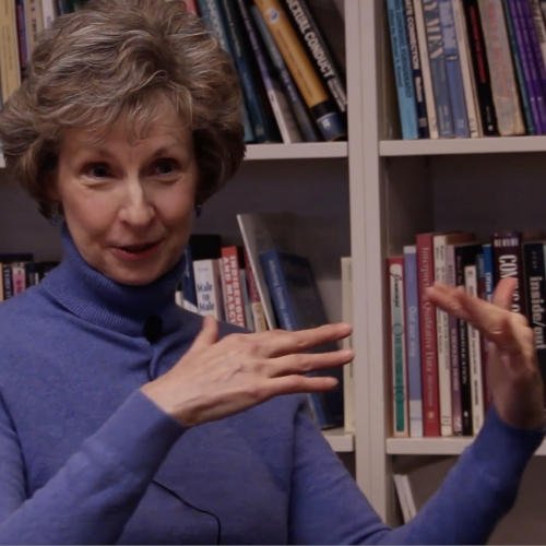 A picture of Professor Janet Jamieson wearing a purple sweater sitting in front of a bookcase, midway through the ASL sign for Star Wars