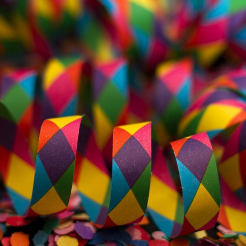 A close up of rainbow coloured confetti tape, sitting in loops on a flat surface