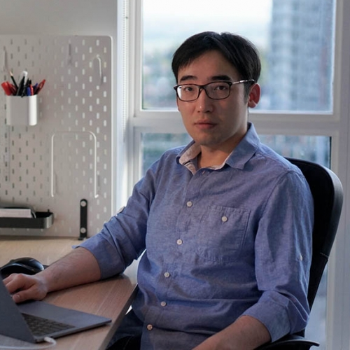 Keyi Tang sitting at a desk in front of a latop and a window with a cityscape. He is wearing a blue shirt and glasses