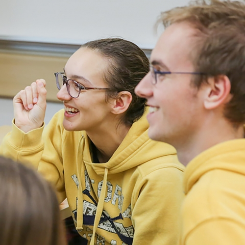 A close up of Paris laughing, and Kelton smiling, both dressed in yellow