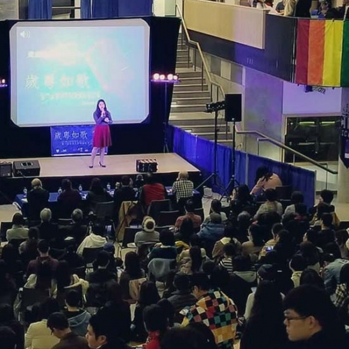 A picture of Zoe Lam onstage at a Cantonese languagae program event in a mall, in front of a crowd of people