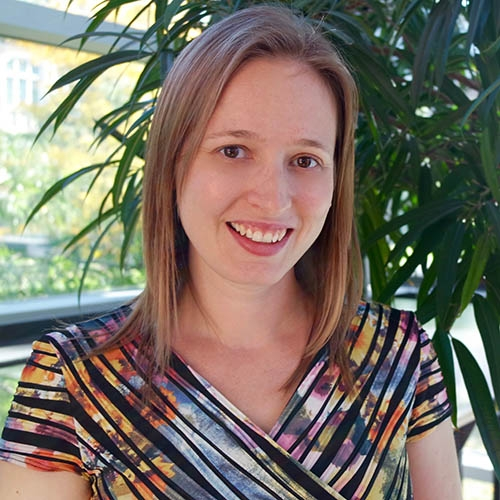 A headshot of Krista Byers-Heinlein standing in front of a plant