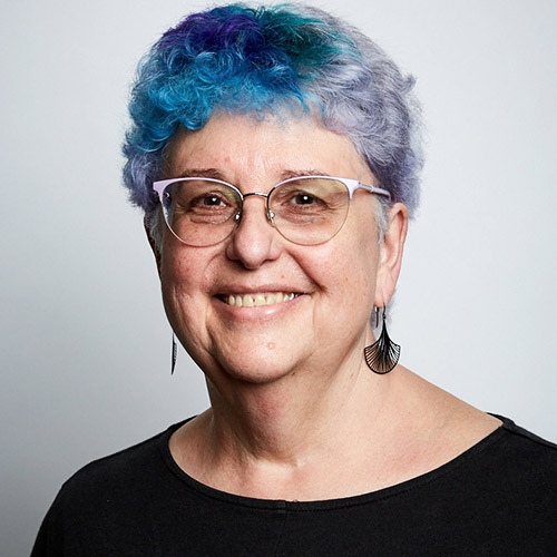 A picture of Professor Catherine Best who is wearing glasses, a black shirt and has blue hair