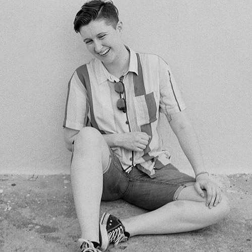 A black and white photo of Bridget Chase sitting against a white wall, laughing.
