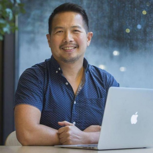 A picture of Ron Darvin smiling, sitting in front of a laptop with arms crossed on the table.