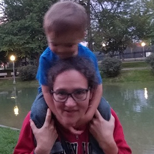 Elena Nicoladis with a child on her shoulders. She is holding the childs knees and wearing a red shirt and glasses, and standing in front of a pond with lights in the background
