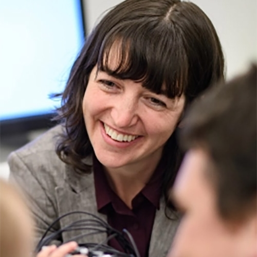 An image of Lauren Emberson smiling as she listens to someone, sitting in front of a projector screen. Part of someones head is blurred in the right foreground
