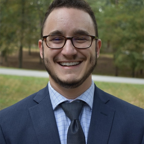 A headshot of Ethan Kutlu smiling, wearing glasses and a suit and tie, with green grass and trees in the background
