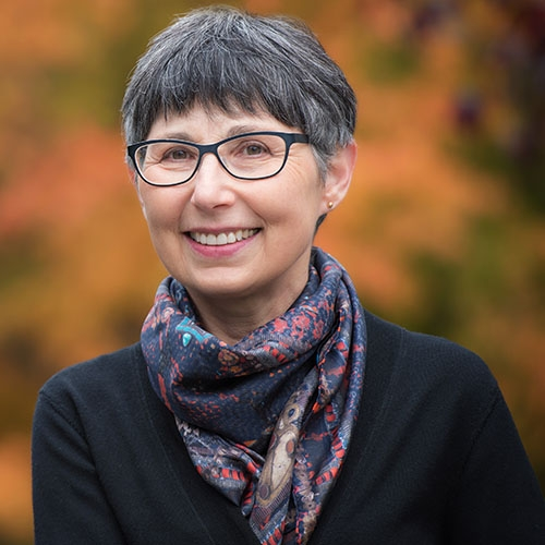 A headshot of Janet Werker standing outside and wearing a scarf