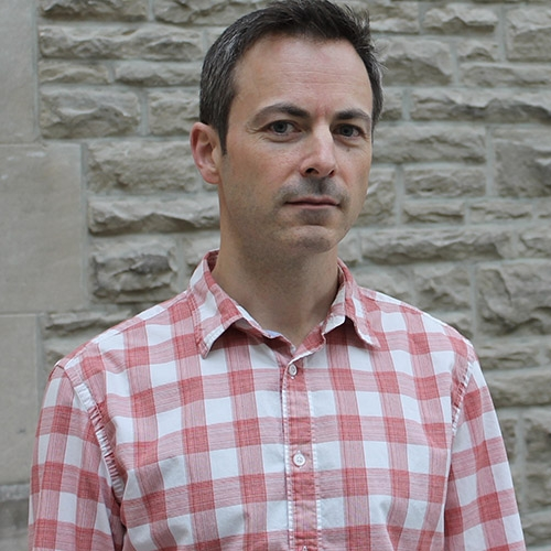 A headshot of Marc Joanisse standing in a checked shirt against a sandy coloured brick wall.