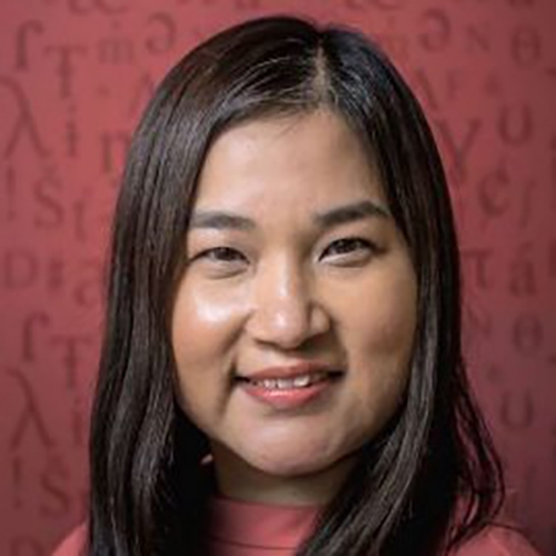 A headshot of Zoe Lam with shoulder length hair, standing against a red background