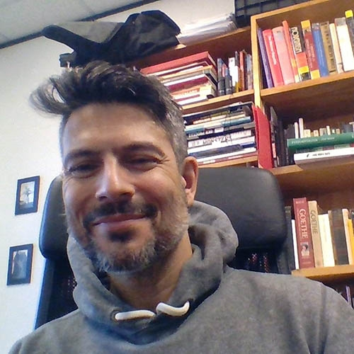 A headshot of Jason Lieblang sitting in front of a bookcase