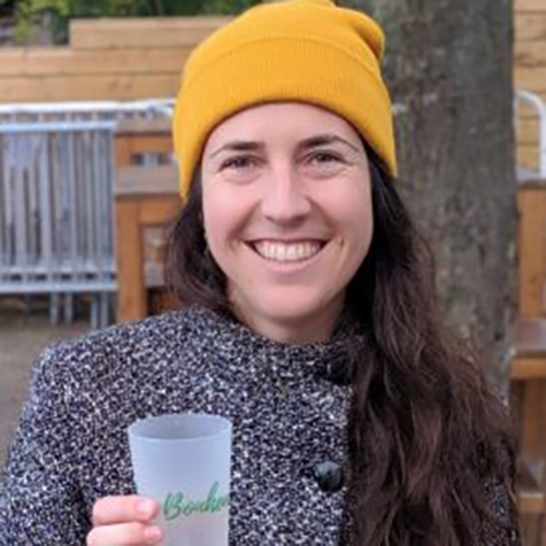 A headshot of Marie-Eve Bouchard holding a glass and wearing a yellow toque